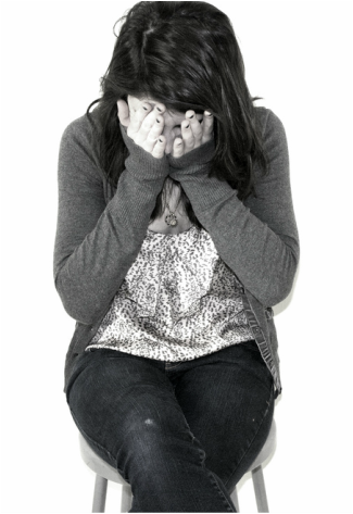 Woman sitting on stool with hands over her face, looking embarrassed